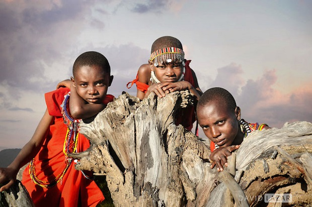 Masai children in Kenya interacting with their own bodies and an uprooted old tree